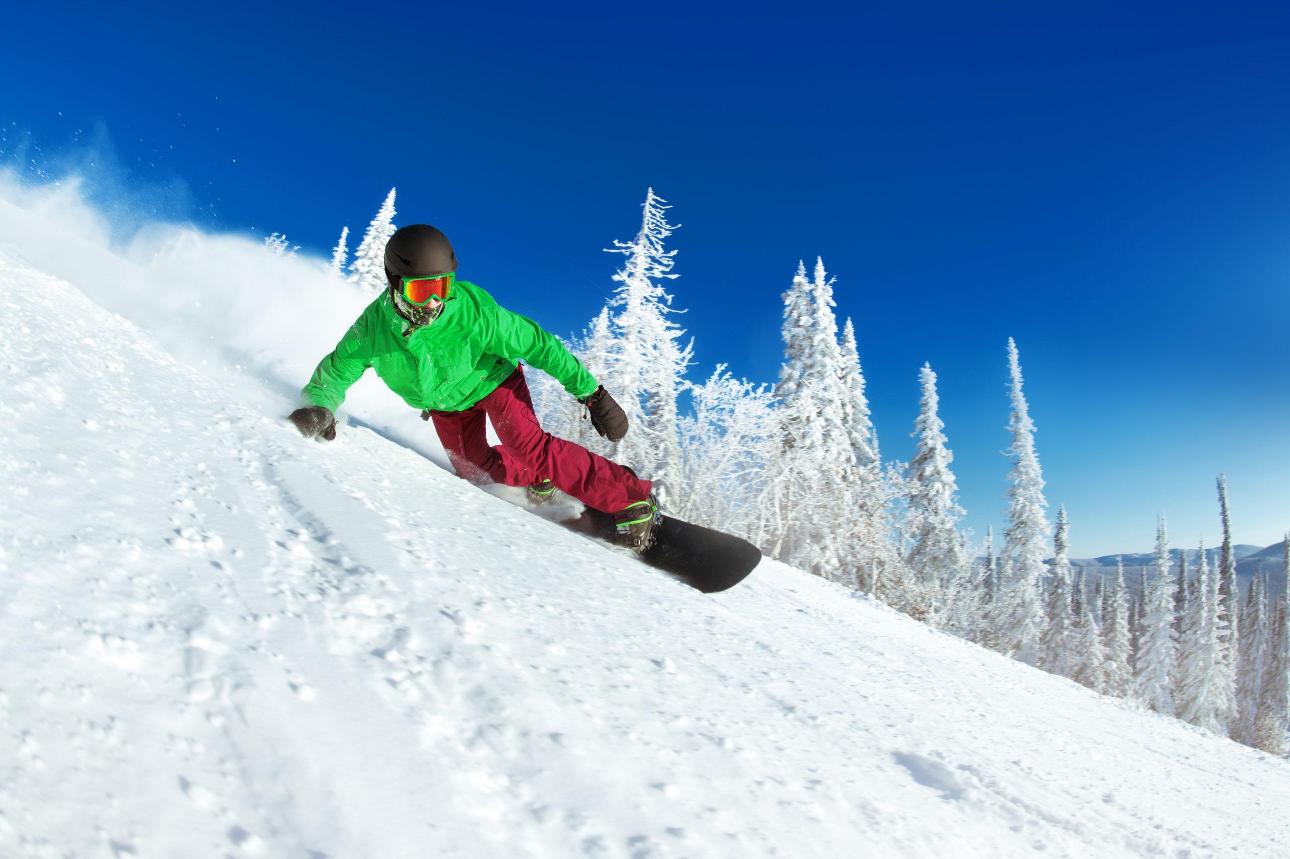 hombre en snowboard descendiendo en una montaña con fondo nevado