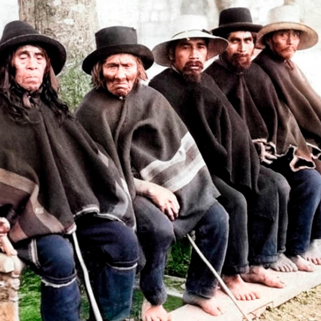 grupo de huilliches sentados mirando a la cámara con ponchos y gorros