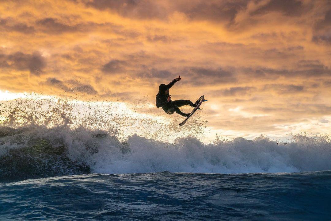 surfista surfeando en olas de playa de pichilemu en atardecer