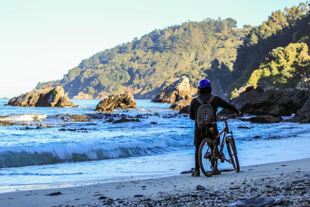 Ciclista mirando el horizonte en dirección al mar en playa los burros
