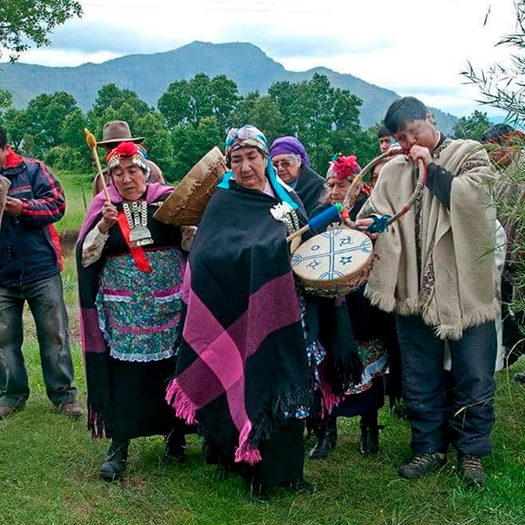 Grupo de mapuche reunidos celebrando el we tripantu mapuche con diversos instrumentos musicales típicos