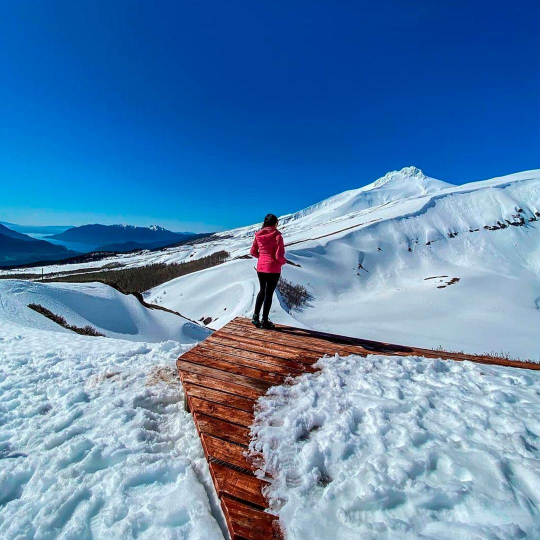 mujer caminando por sendero nevado