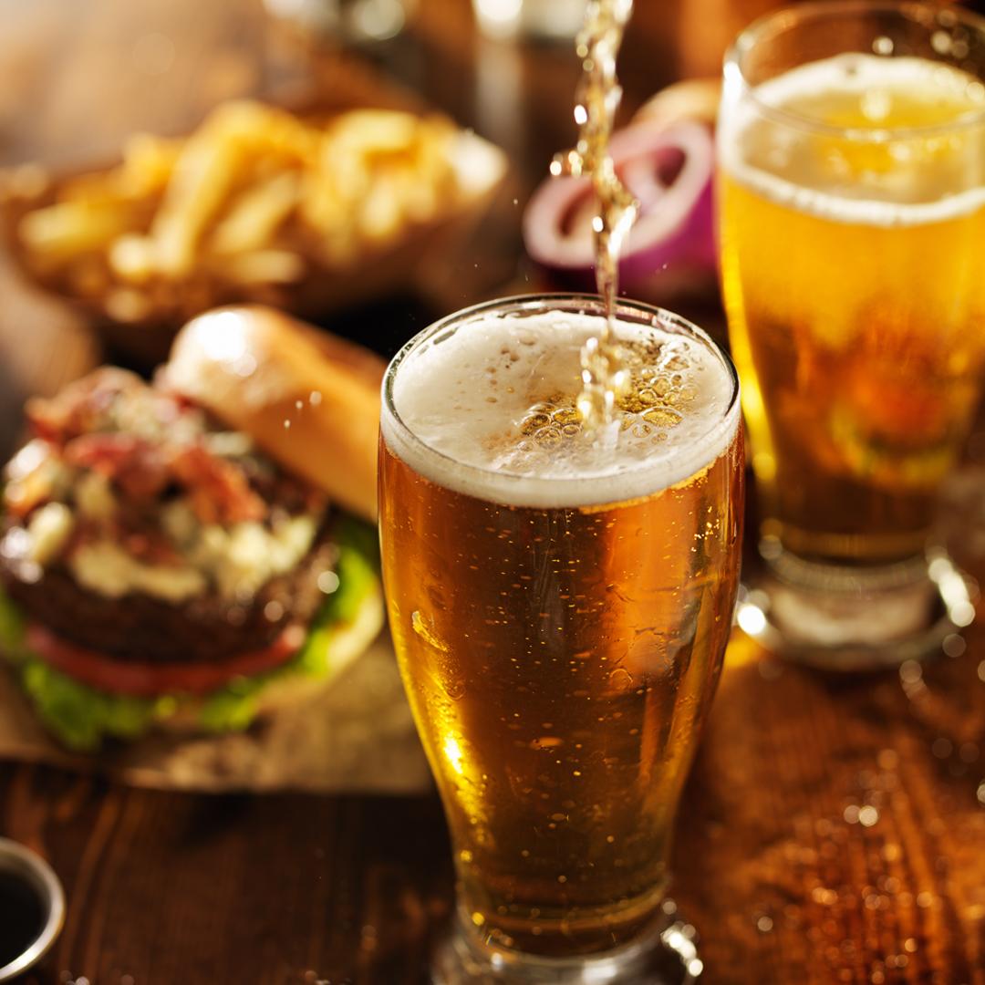 fotografía cervezas servida en mesa con comida y picoteo