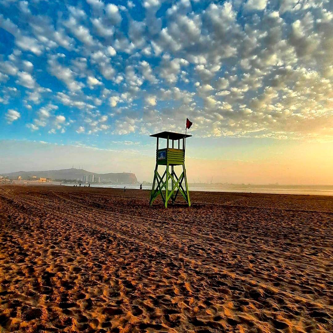 fotografía de playa en atardecer y torre de salvavidas