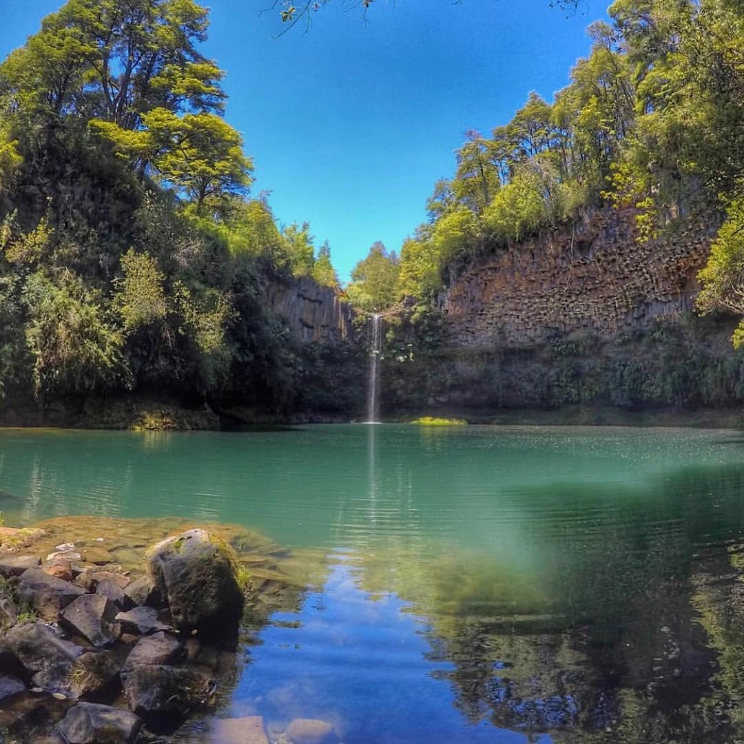 fotografía del salto lleno de vegetación y aguas azulinas
