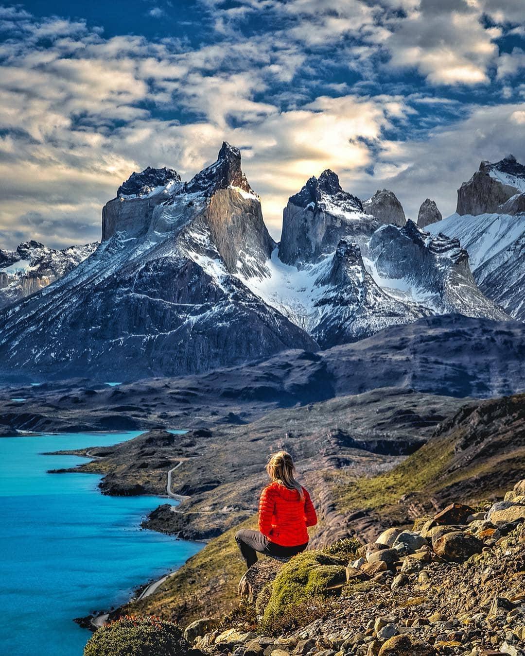 Mujer sentada contemplando el paisaje de las Torres del Paine